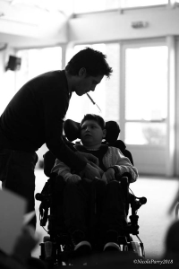 silhouette of a man holding a syringe in his mouth to give medication via the tube inserted in a boy who is in a wheelchair.