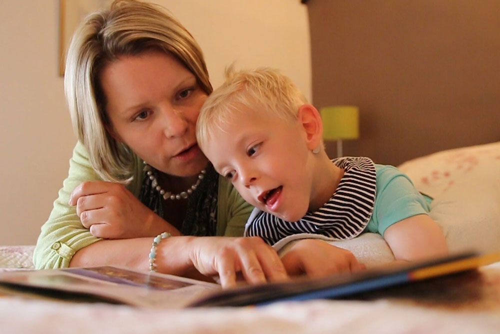 young boy with blond hair being read a story by his motherg